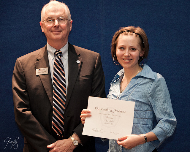 Olga receiving the Outstanding Graduate Award with President Donald P. Christian