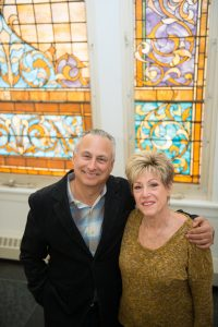 Bruce and Sandi in front of the stained glass windows in Old Main on a recent visit to the campus.